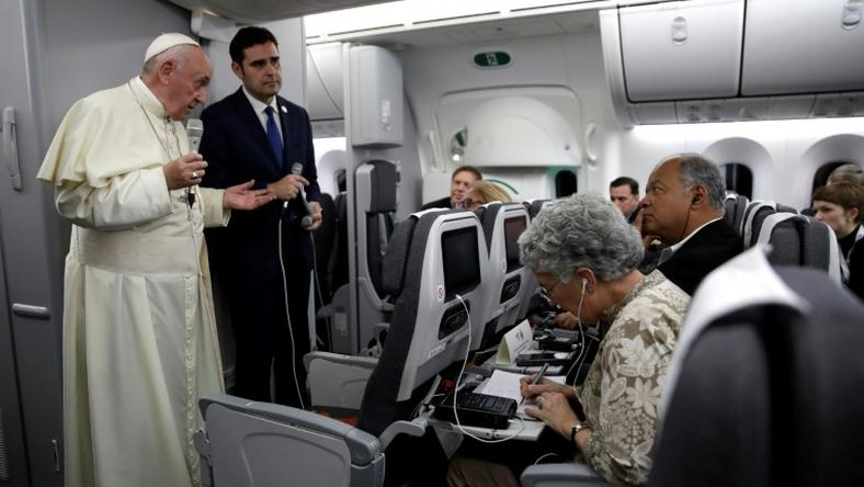 Pope Francis, flanked by Vatican spokesman Alessandro Gisotti (right) anwers journalists questions in the plane following the take off from Panama City on January 27, 2019 after participating in World Youth Day