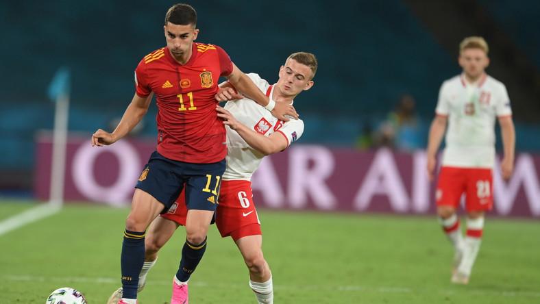 Ferran Torres (L) w starciu z Kacprem Kozłowskim (P) podczas meczu Polski z Hiszpanią
