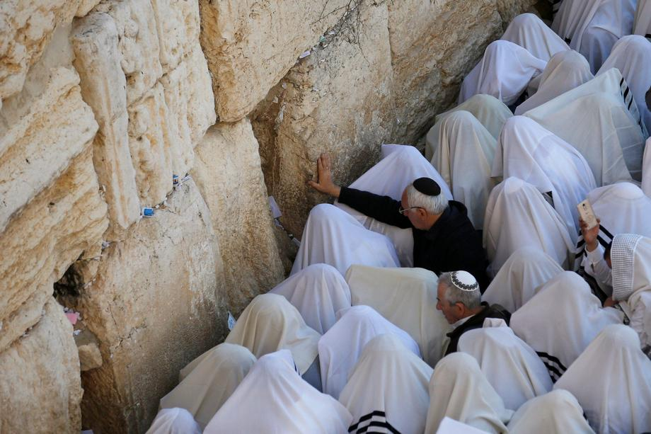 Jewish worshippers wrapped in prayer shawls participate in the priestly blessing prayer on the holid