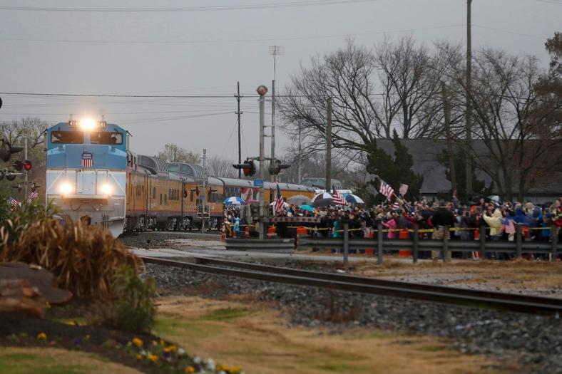 People lined up along the railroad tracks, waving American flags flags to pay their respects.