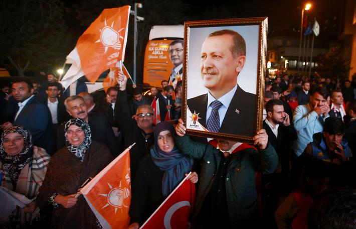 People wave flags and hold a portrait of Turkish President Tayyip Erdogan outside the AK Party headq