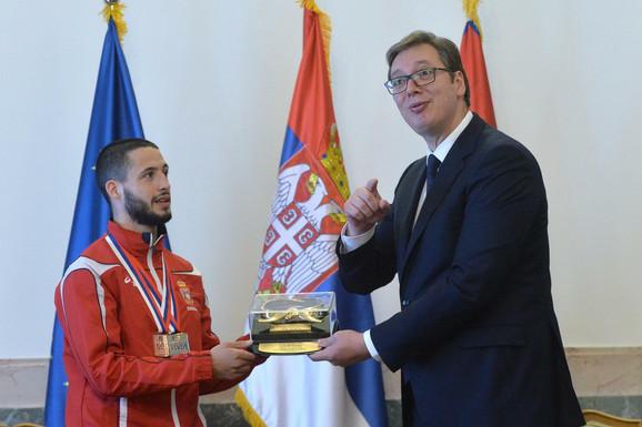 Karate reprezentativac Stefan Joksić uručuje plaketu Saveza predsedniku Aleksandru Vučiću