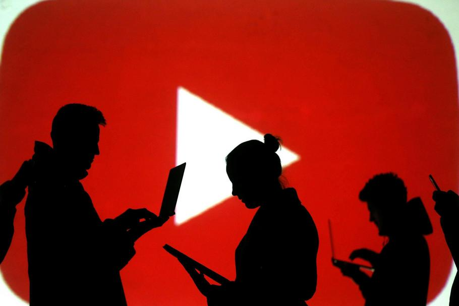 Silhouettes of laptop and mobile device users are seen next to a screen projection of Youtube logo i