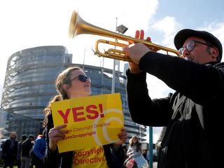Demonstrators take part in a protest in front of the European Parliament as MEPs debate on modificat