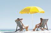 stock-photo-beach-summer-couple-on-island-vacation-holiday-relax-in-the-sun-on-their-deck-chairs-under-a-yellow-97745612
