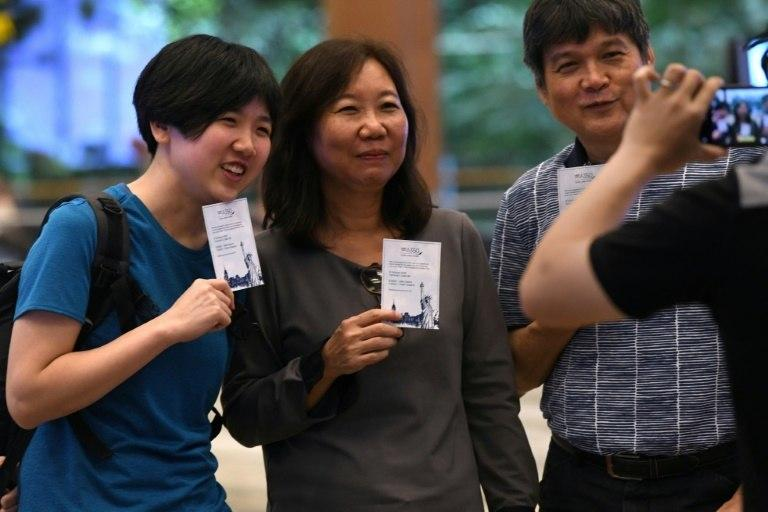Singaporean William Chua (R) with family members, all passengers of flight SQ22, Singapore Airlines' inaugural non-stop flight to New York pose with souvenir cards after their their check-in at Changi International Airport in Singapore on October 11, 2018