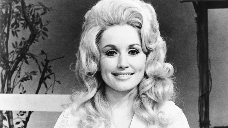 """Dolly Parton urodziła się jako jedno z dwanaściorga dzieci farmera Roberta Lee Partona i Avie Lee Parton. Jej dziadek był kaznodzieją zielonoświątkowym, a mała Dolly po raz pierwszy przed publicznością stanęła w kościele. Karierę muzyczną rozpoczęła już w latach 60. W roku 1967 wydała pierwszy album """"Hello, I'm Dolly. Do jej największych przebojów należą piosenki """"Jolene"""", """"9 to 5"""" oraz """"Just When I Need You Most"""". To ona napisała piosenkę """"I Will Always Love You"""", która w wykonaniu Whitney Houston stała się megahitem"""