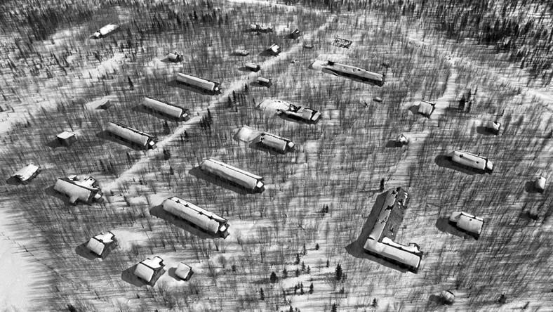 Typowy obóz dla blisko 500 więźniów. Siedem baraków w dwóch rzędach dla około 80 więźniów każdy, pomiędzy nimi droga prowadząca do linii kolejowej przez wachtę do łagrowej jadalni (z lewej). Dwa małe budynki w lewym dolnym rogu to prawdopodobnie piekarnia i łaźnia. Z prawej, za ogrodzeniem obozu, budynek strażników i administracji obozowej (w kształcie litery L) oraz magazyny narzędzi i żywności. Od lat dwudziestych do pięćdziesiątych XX wieku w łagrach przetrzymywano ponad 20 milionów skazańców. Życie straciło tam 2 miliony więźniów.