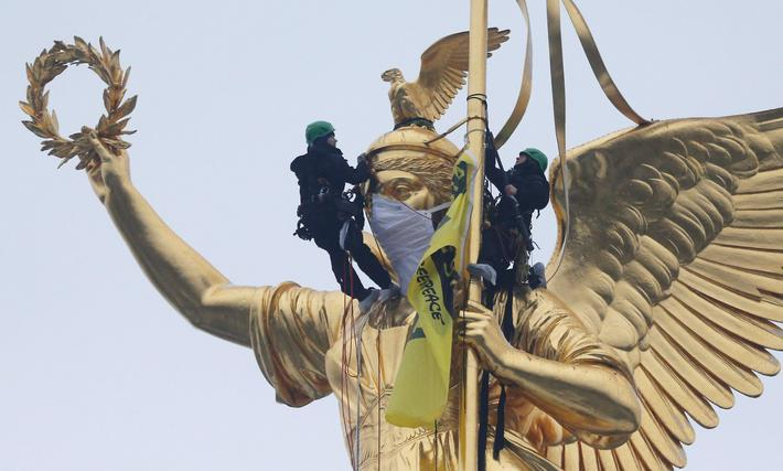 Greenpeace activists climb the Golden Victoria monument on top of the Victory Column and install a b