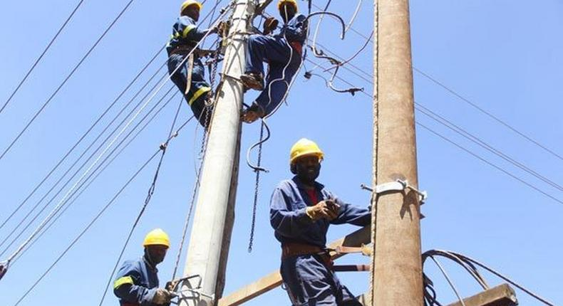 Kenya Power workers install concrete pole