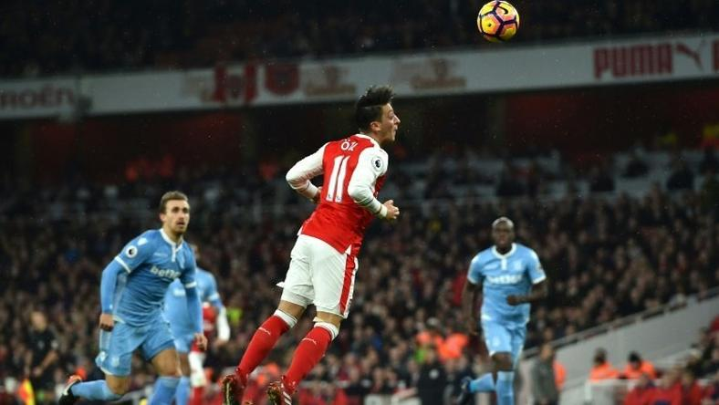Arsenal's German midfielder Mesut Ozil (C) heads the ball to score their second goal against Stoke City at the Emirates Stadium in London on December 10, 2016
