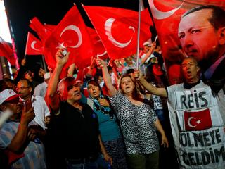People shout slogans and wave Turkish national flags as they have gathered in solidarity night after