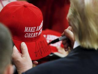 U.S. Republican presidential candidate Trump signs a hat at a campaign rally in West Chester