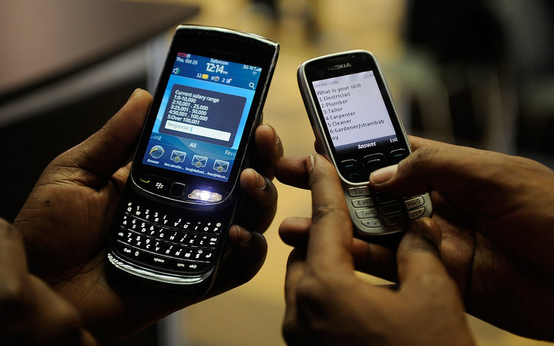 File image of mobile phone users engaged on their handsets