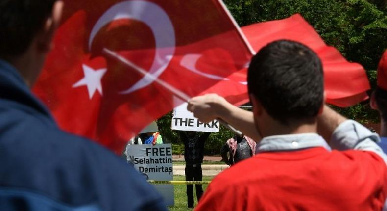 Pro-Erdogan supporters wave Turkish flags at anti-government protesters in front of the White House in Washington, DC on May 16, 2017
