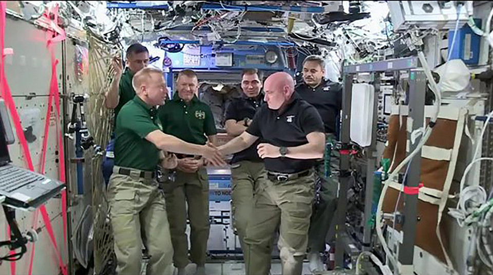 NASA astronauts Scott Kelly and Tim Kopra shake hands as Kelly turns over command aboard the International Space Station