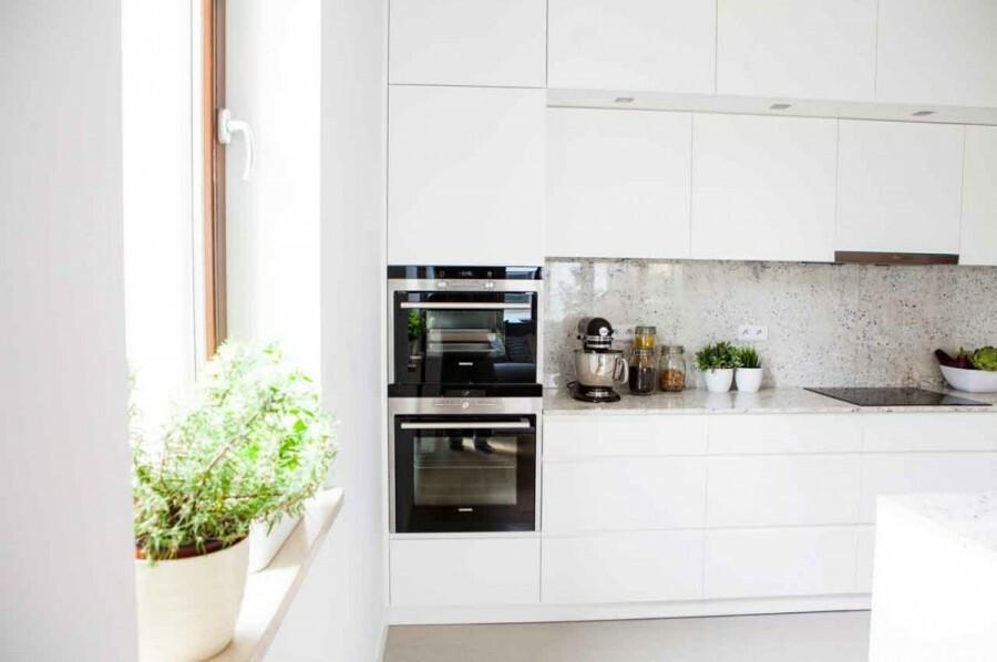 Zabudowa kuchenna z wyspą oraz szafkami dolnymi i dwoma rzędami górnych, zakończonych po bokach wysokimi słupkami, zapewnia dużo miejsca do przechowywania.