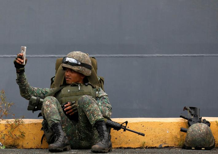 A Philippine marine soldier takes a selfie with his phone during their arrival from Marawi at port a