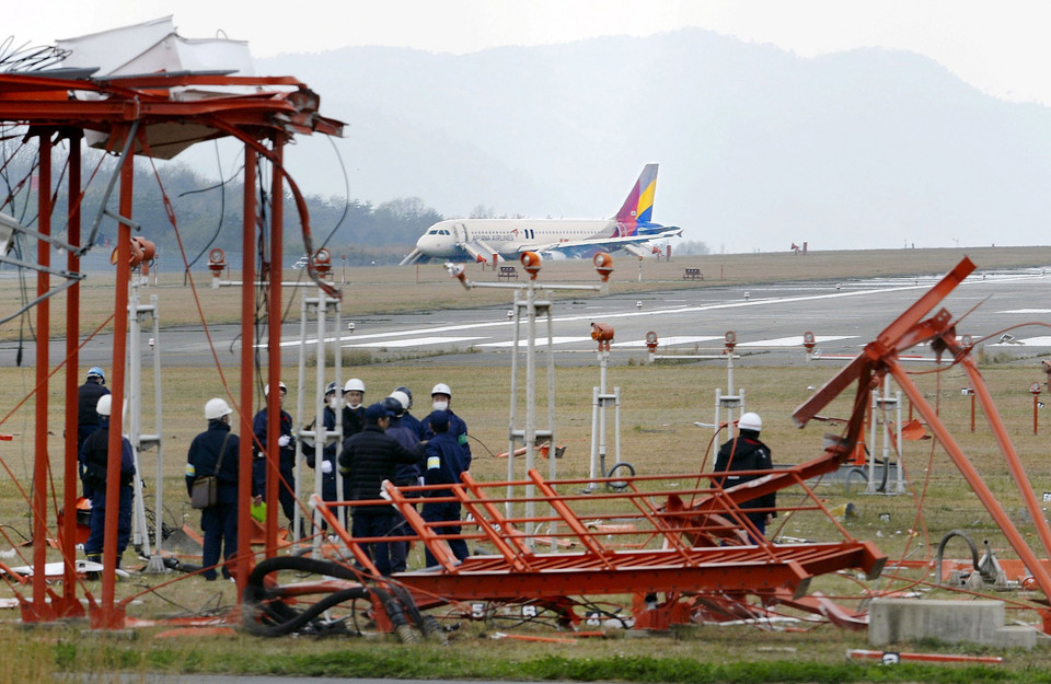Police officers investigate broken wireless communication equipment, which an Asiana Airlines airplane from Incheon airport is believed to have struck before running off the runway at Hiroshima airport, in Mihara, Hiroshima prefecture