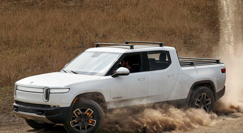 Watch the Tesla Cybertruck rival Rivian R1T drift around the desert and crawl up boulders in new testing videos