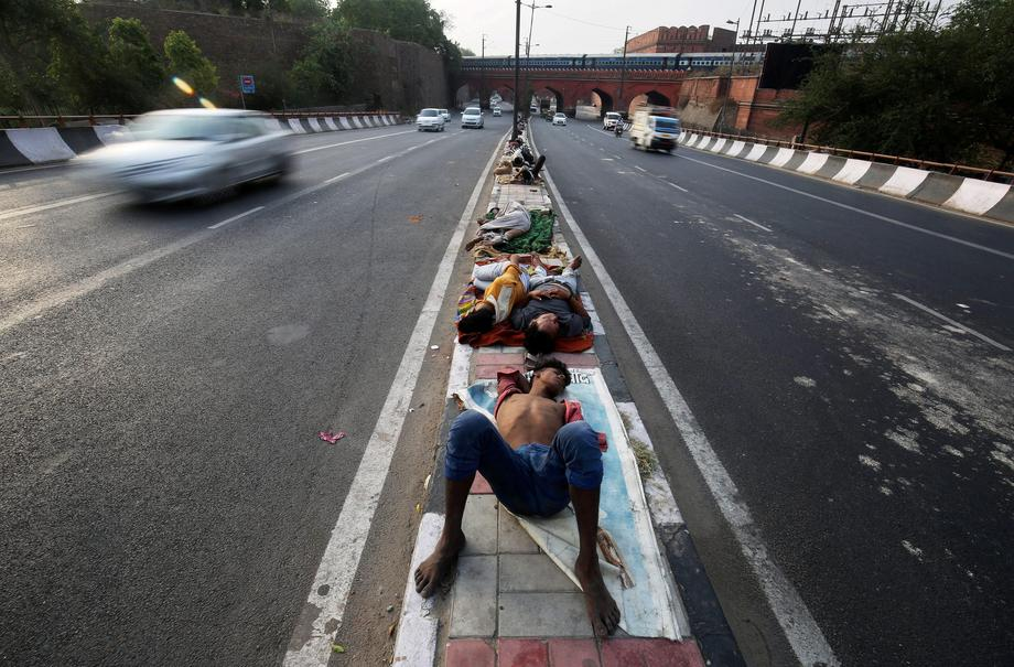 People sleep on a road divider in New Delhi