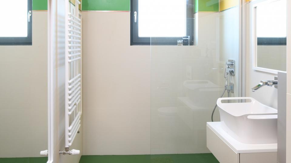 Szafkę i ceramikę sanitarną umieszczona na jednej ścianie, w głębi pomieszczenia, we wnęce znalazł się prysznic.