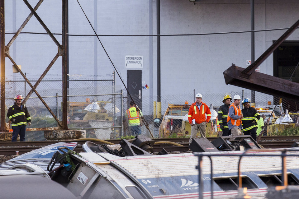 Emergency workers survey the remains of a derailed Amtrak train in Philadelphia, Pennsylvania