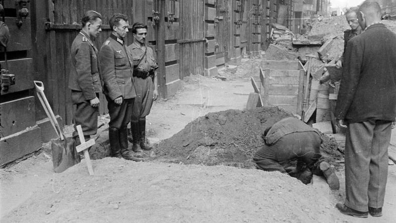 Składanie zwłok do grobu wykopanego w obrębie chodnika, usytuowanego prostopadle do ściany kamienicy. Pochyla się nad nią jeden z jeńców niemieckich, zapewne poprawia układ zwłok. Za nim dwóch mężczyzn w cywilnych ubraniach. Między jamą a ścianą kamienicy stoją dwaj żołnierze niemieccy, bluzy mundurowe bez pasów, brak nakryć głów. Obok nich mężczyzna w bryczesach wpuszczonych w buty - oficerki, spiętych niemieckim pasem wojskowym z charakterystyczną klamrą i z koalicyjką, przy pasie kabura pistoletu i ładownice, koszula z podwiniętymi rękawami wpuszczona w spodnie. Na pierwszym planie, w obrębie chodnika sporych rozmiarów nasyp grobowy z krzyżem - prawdopodobnie mogiła zbiorowa. O ścianę kamienicy oparte łopaty, dalej - drewniany szalunek barykady przy gmachu PKO i ściana kamienicy Świętokrzyska 38/40/42 z witrynami zasłoniętymi deskami. Data: 2 - 6 sierpnia 1944r.