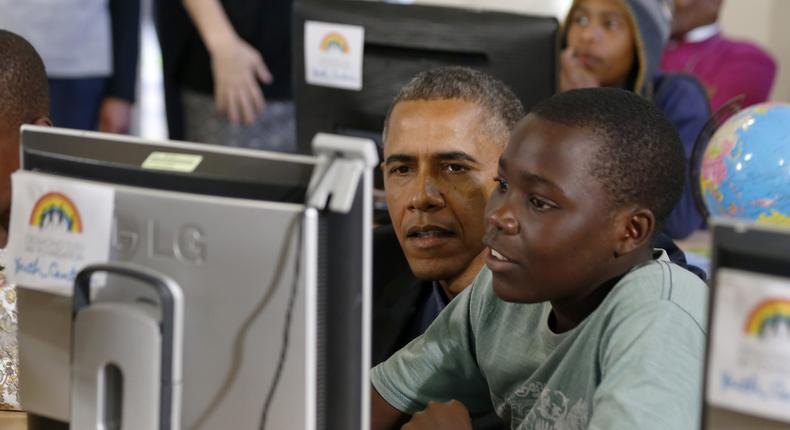 Former US President Barack Obama looks at a computer with youth as he tours the Desmond Tutu HIV Foundation Youth Centre in Cape Town
