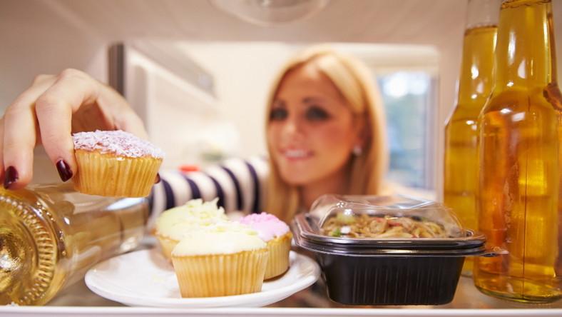 Kobieta wyjmuje słodycze z lodówki. Zachcianki żywieniowe