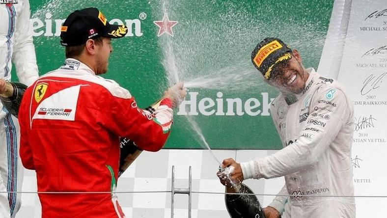 Mercedes F1 driver Lewis Hamilton (R) of Britain and Ferrari F1 driver Sebastian Vettel of Germany celebrate after the race.
