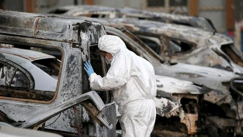 A French police officer inspects burned vehicles outside the Splendid Hotel in Ouagadougou, Burkina Faso, file.
