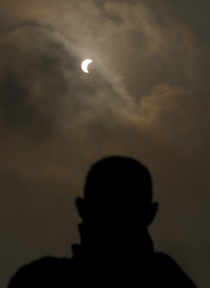 A Buddhist monk watches a partial solar eclipse in Phnom Penh, Cambodia