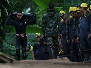 A diver carries an oxygen tank as he leaves the Tham Luang cave complex, where 12 boys and their soc
