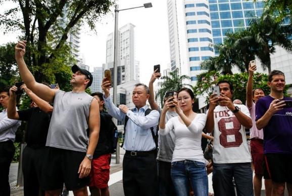 Ljudi u Singapuru slikaju Kimov automobil