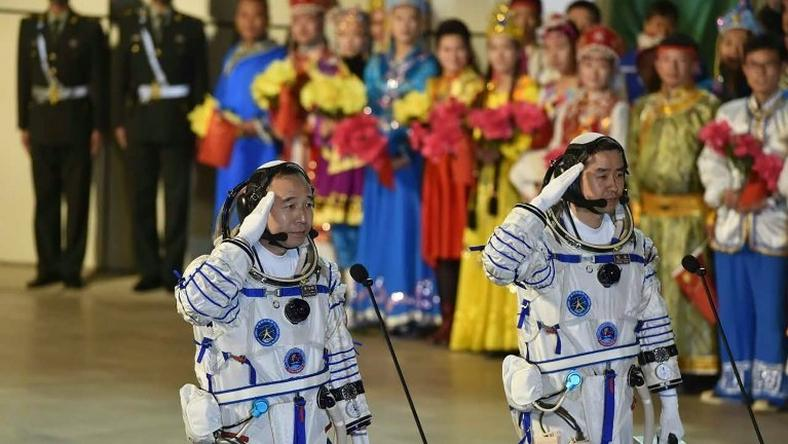 Chinese astronauts Jing Haipeng (L) and Chen Dong salute during the send-off ceremony of the Shenzhou-11 manned space mission, at the Jiuquan Satellite Launch Center in north-western Gansu Province, on October 17, 2016
