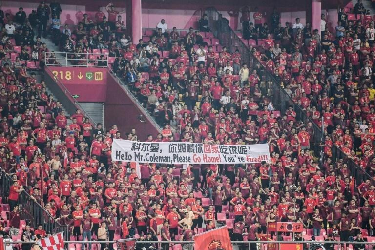 "This photo taken on May 11, 2019 shows fans of Hebei China Fortune FC holding a banner that read ""Hello Mr. Coleman, please go home! You're fired!!!"" during the Chinese Super League (CSL) football match between Hebei China Fortune and Henan Jianye in Langfang in China's northern Hebei province. Chris Coleman is battling to save himself from the sack after angry fans of struggling Hebei China Fortune demanded the former Wales manager be fired."