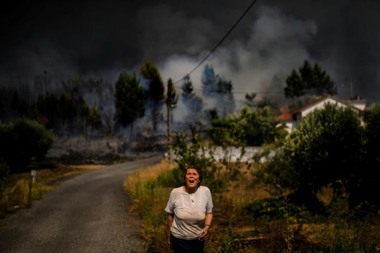 A villager shouts for help as a wildfire approaches a house in the village of Casas da Ribeira in central Portugal on July 21