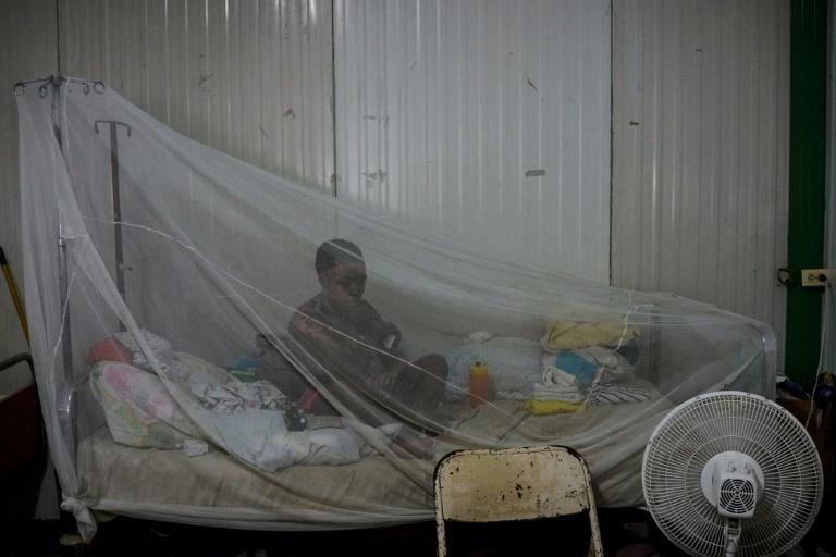 A patient sits on her bed protected by a net at a preoperative ward during the doctors' strike