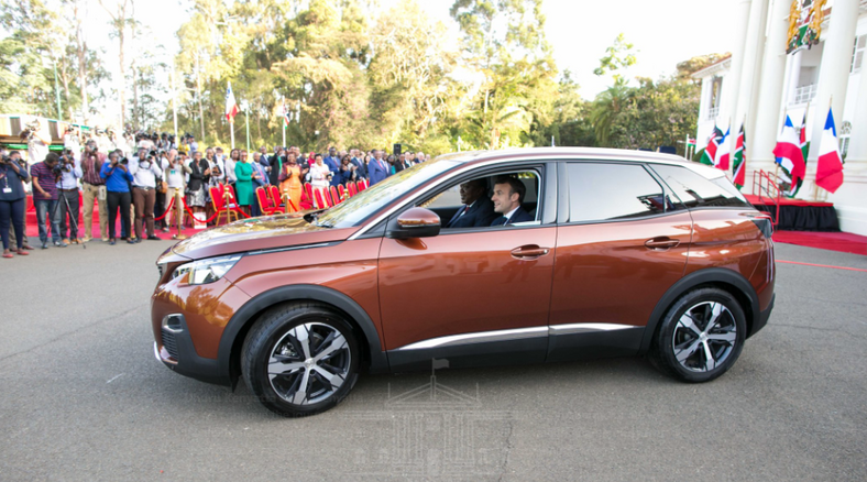 President Uhuru Kenyatta and his French counterpart President Emmanuel Macron inside the brand-new Peugeot 3008 at the Statehouse during the unveiling ceremony of the newly assembled Sports Utility Vehicle (SUV).