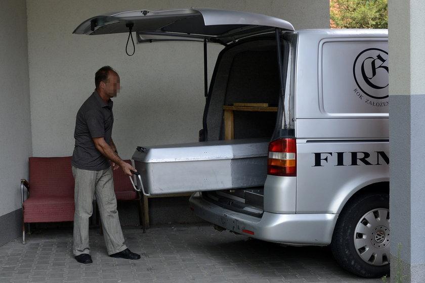 Pracownik firmy pogrzebowej wkłada trumnę do karawanu
