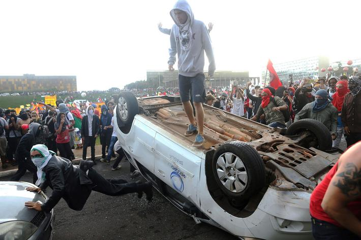 Anti-government demonstrators gesture atop a press car of Tv Record as they attend a demonstration a