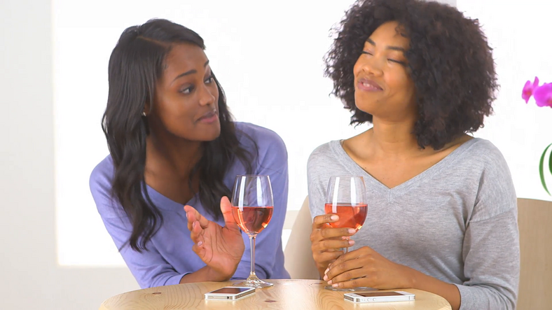 Friends having a chat over a bottle of wine. [Credit: Video Blocks]