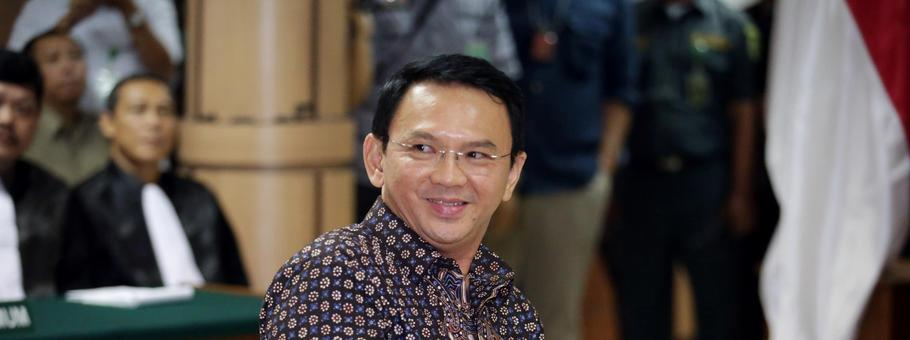 Jakarta's Governor Basuki Tjahaja Purnama smiles to the visitors inside the courtroom during his blasphemy trial at the North Jakarta District Court in Jakarta
