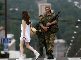 An armed man smiles at a girl