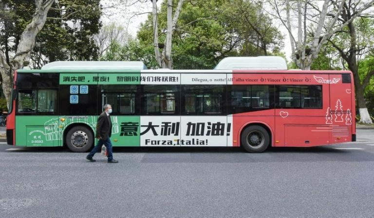 A man wearing a face mask in Hangzhou, China walks past a bus with a message supporting Italy in its efforts against the COVID-19 coronavirus