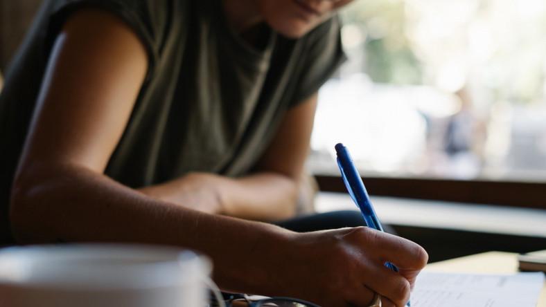 Kobieta robi notatki. Pisanie