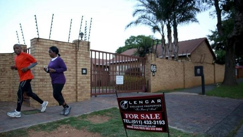 "A couple jogs past a ""for sale"" sign outside a house in Johannesburg, February 1, 2016. REUTERS/Siphiwe Sibeko"