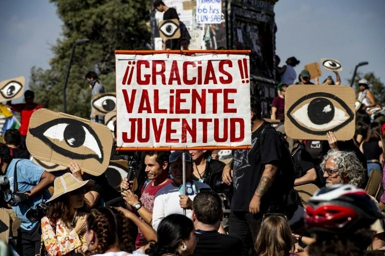 "Demonstrators hold placards depicting eyes -- in reference to protesters' eyes damaged by pellets -- and a sign reading ""Thanks, brave youth"" during a protest in Santiago, on December 10"