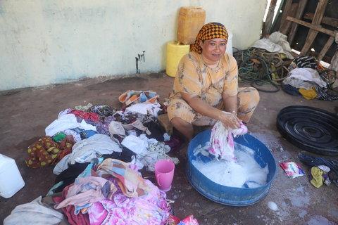 Woman washing clothes saltwater kiunga kenya